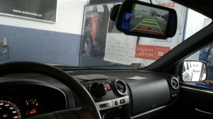 Monitor montowany na lusterku wstecznym. Na ekranie obraz z kamery cofania.